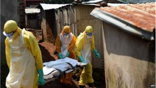 "Health workers from Sierra Leone""s Red Cross Society Burial Team 7 carry a corpse out of a house in Freetown on November 12, 2014"