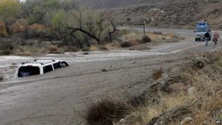 A television news crew walks away from a vehicle caught in an overnight mudslide on Soboba Road near Gilman Springs Road in San Jacinto, California 4 December 2014