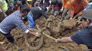 Villagers dig out a motorcycle buried in the mud after a landslide hit the village of Sampang in Banjarnegara, December 13, 2014