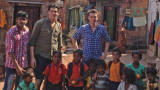 Gandys Rob (L) and Paul (R) Forkan pose with youngsters in Vasco da Gama on the west coast of India.