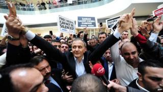 Ekrem Dumanli, editor-in-chief of Zaman newspaper, waves to staff and supporters, while being arrested by counter-terror police at the newspaper's headquarters in Istanbul.
