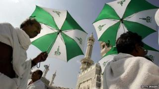 Pilgrims using umbrellas to shade themselves from the sun in Mecca
