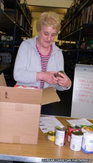 A volunteer sorts food into boxes