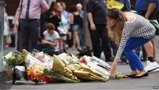 A woman lays flowers at a memorial in Sydney (16 Dec 2014)