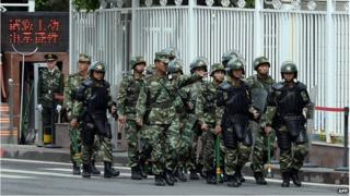 This file picture taken on on 23 May 2014 shows fully armed Chinese paramilitary police patrol a street in Urumqi, the capital of farwest China's Muslim Uighur homeland of Xinjiang.