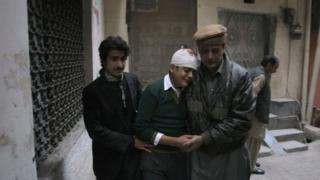 Relatives comfort injured student Mohammad Baqair in Peshawar, 16 December