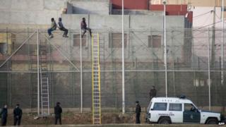 Migrants on a fence in Melilla (file pic)