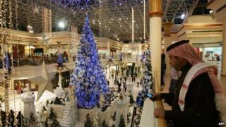 A Christmas tree in a Dubai shopping centre, with a Emirati man in the foreground