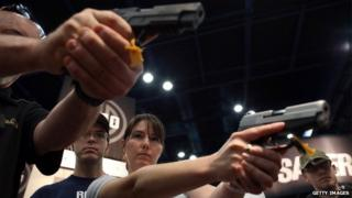 Attendees hold handguns in the Sig Sauer booth during the 2013 NRA Annual Meeting and Exhibits at the George R Brown Convention Center 4 May 2014
