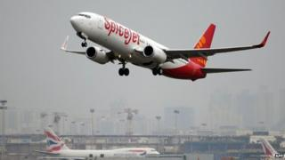An Indian-operated SpiceJet Boeing 737-800 aircraft (foreground) takes off in Mumbai