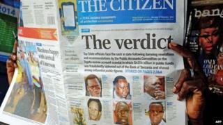 A newspaper vendor holds a copy of The Citizen newspaper in Dar es Salaam, Tanzania on 27 November 2014