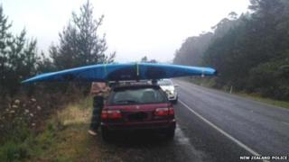 The car with the kayak strapped to the roof