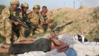 British soldiers with Iraqi detainees, who are bound and lying face-down on the ground