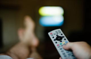 Remote control and feet up in front of TV