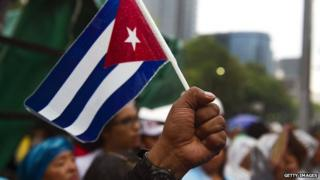 A man raises his fist with a Cuban flag in Mexico City on 26 July 2011