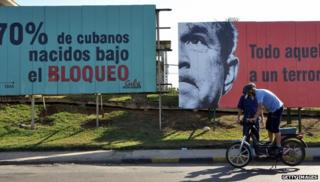 A Cuban checks his motorcycle in front of political billboards allusive to the US embargo on Cuba, on April 20, 2009 in Havana.