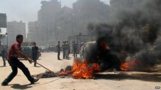 Supporters of the ousted Islamist president block a road with burning tires in Cairo's northern district of Matariya on August 14, 2014