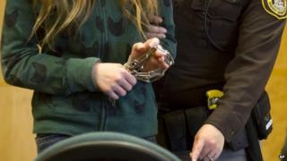 One of two 12-year-old girls accused of stabbing a classmate to please the fictional horror character Slender Man is led into a courtroom for a hearing Waukesha, Wisconsin 12 November 2014
