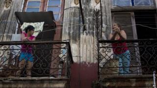 Two women talk on a Havana balcony