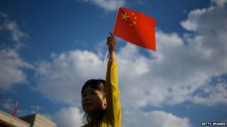 A girl waves a Chinese flag on Tiananmen Square in Beijing on 1 October, 2014