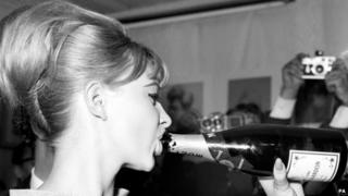 Mandy Rice-Davies drinking a bottle of champagne in July 1963