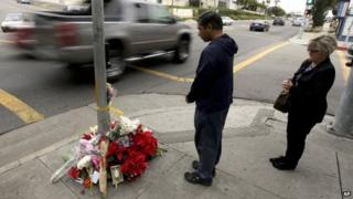 Mourners pay their respects at a memorial in Redondo Beach, California, on 18 December 2014
