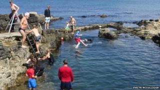 People diving into a sea pool at Portstewart