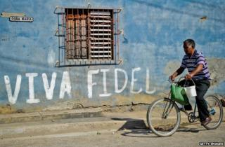 Man cycles past 'Viva Fidel' sign in Havana, Cuba