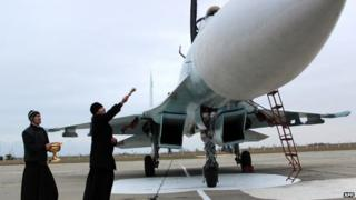 A Russian Orthodox priest blesses a SU-27 SM fighter jet at Belbek military airport near Sevastopol, 26 Nov