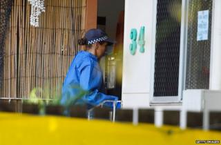 A policewoman enters the house where the murders took place in Cairns, Australia, 21 December