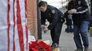 Police officers bring candles to an impromptu memorial near the site where two police officers were killed in the Brooklyn borough of New York, Sunday, Dec. 21, 2014
