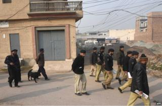 Pakistani police search around the school in Peshawar, 21 December