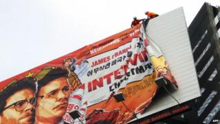 "Workers remove the poster for ""The Interview"" from a billboard in Hollywood, California, 18 December 2014."