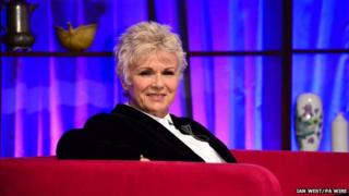 Julie Walters sitting on sofa on stage at Bafta