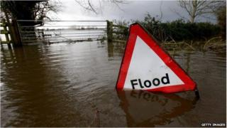 """A """"flood"""" sign partly submerged on a flooded rural road"""