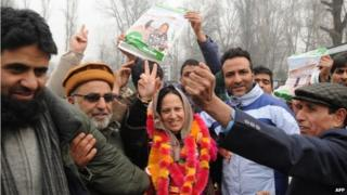 Peoples Democratic Party (PDP) candidate Asiya Naqash (C) gestures after winning the Hazratbal constituency, in Srinagar on December 23, 2014