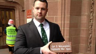 Cpl Stewart McLaughlin's son Stewart hold the memorial brick