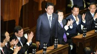 Japan's Prime Minister Shinzo Abe (C) stands after being re-elected as Japan's premier, as lawmakers applaud in the Lower House of the Parliament in Tokyo, Japan, 24 December 2014