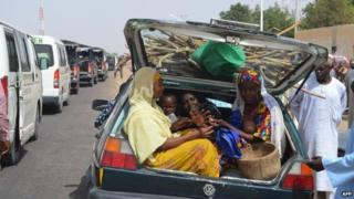 Women and children gather into a car's trunk as villagers flee the village of Jakana, outside Maiduguri, Borno State, Nigeria, on 6 March 2014