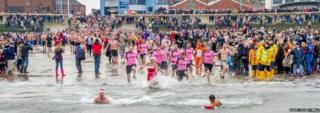 Swimmers run into the sea