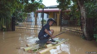 A man makes his way to his house submerged in floodwaters in Pengkalan Chepa, near Kota Bharu