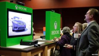 A man and woman look at an Xbox One