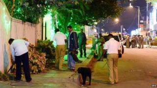 Indian police personnel and bomb squad check for evidence after bomb blast site on Church Street, in Bangalore, India on 28 December 2014