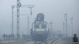 Passengers crowd atop a train as they travel on a cold winter morning at a railway station in Ghaziabad on the outskirts of New Delhi December 29, 2014