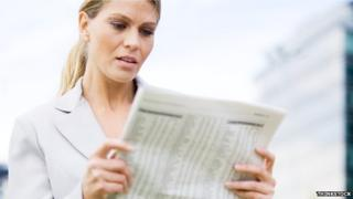woman reads financial pages