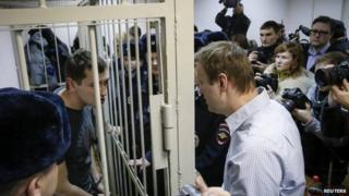 Alexei Navalny (right) speaks to his brother Oleg (left) after the brothers are given difference sentences by a judge in Moscow (30 December 2014)