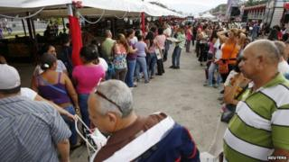 People stand in line to buy food at a state-run street market in Caracas in this 13 November, 2014 file photo.