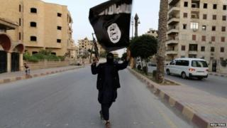 A member loyal to the IS waves an IS flag in Raqqa