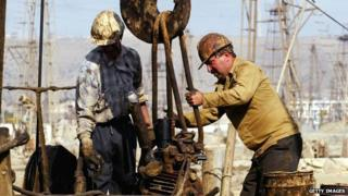 Oil workers operate on a well.