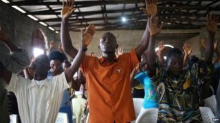 Church members pray during a Sunday service on 24 August 2014 in Dolo Town, Liberia
